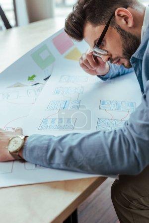 Photo pour Concentration sélective du concepteur de l'interface utilisateur dans les lunettes en regardant les papiers tissés - image libre de droit