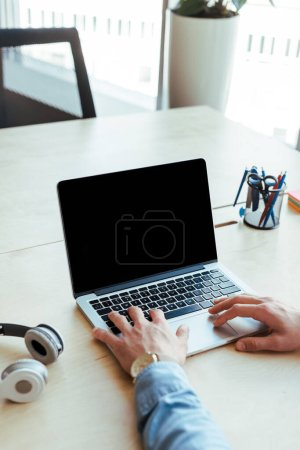 Partial view of IT worker using laptop near headphones at table in coworking space