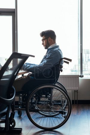 Photo for Selective focus of concentrated disabled IT worker on wheelchair working in coworking space - Royalty Free Image