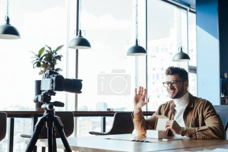 Photo for Blogger in front of digital camera waving hand, smiling and holding opened box at table in coworking space - Royalty Free Image