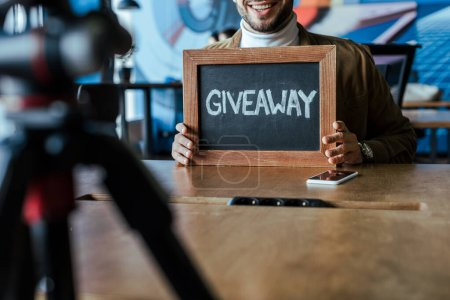 Photo for Cropped view of blogger showing board with giveaway lettering and smiling at table in coworking space - Royalty Free Image