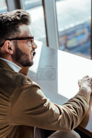 Photo for High angle view of IT worker smiling and talking on smartphone at table near windows - Royalty Free Image