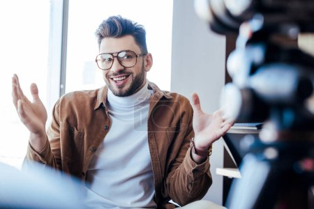 Photo pour Focus sélectif du blogueur dans les lunettes souriant et gesticulant près des fenêtres - image libre de droit