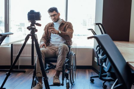 Selective focus of disabled blogger on wheelchair pointing with finger in front of digital camera near windows