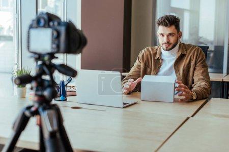 Foto de Enfoque selectivo de blogger con caja cerca de portátil en la mesa delante de la cámara digital. - Imagen libre de derechos