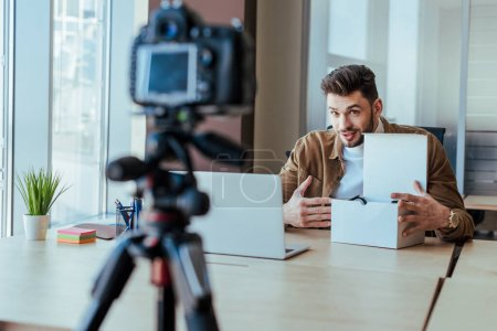 Selective focus of blogger pointing at box near laptop at table in front of digital camera