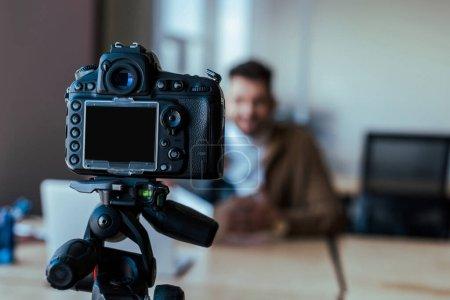 Photo pour Mise au point sélective de la silhouette du blogueur devant l'appareil photo numérique - image libre de droit