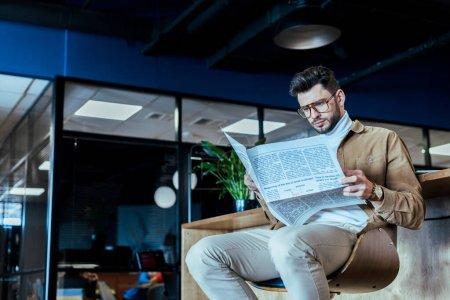 Photo pour Vue à faible angle du travailleur informatique lisant un journal sur une chaise dans un espace de coworking - image libre de droit