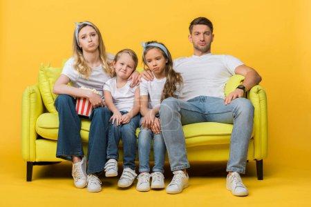 sad family watching movie on sofa with popcorn bucket on yellow