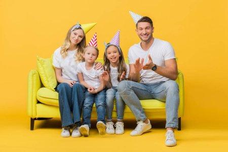 Foto de Feliz familia en cumpleaños partido gorras aplaudiendo en sofá en amarillo - Imagen libre de derechos