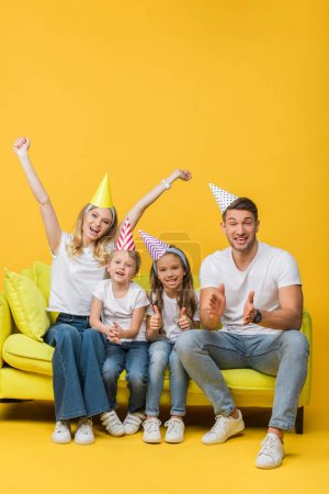 Photo for Happy family in birthday party caps applauding and showing thumbs up on sofa on yellow - Royalty Free Image