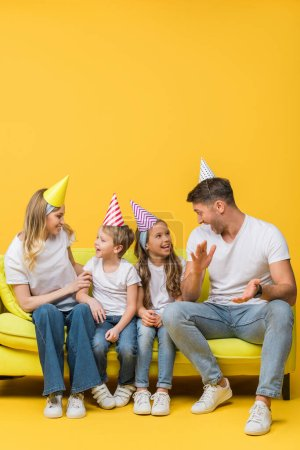 Photo for Cheerful family in birthday party caps applauding on sofa on yellow - Royalty Free Image