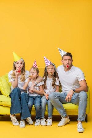Photo pour Heureux parents et enfants dans les casquettes de fête d'anniversaire avec ventilateurs sur canapé sur jaune - image libre de droit
