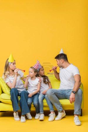 Photo pour Joyeuse famille dans les chapeaux de fête d'anniversaire avec des ventilateurs sur le canapé sur jaune - image libre de droit
