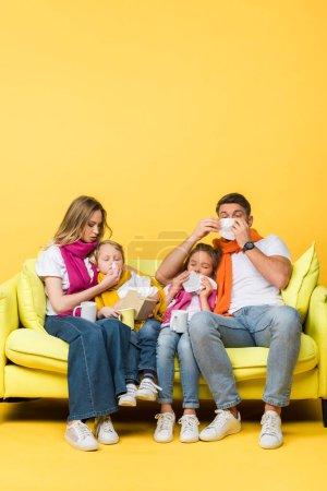 Photo pour Famille malade avec des serviettes ayant le nez qui coule tout en étant assis sur le canapé sur jaune - image libre de droit