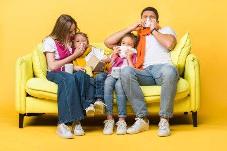 Photo pour Famille malade avec des enfants tenant des serviettes et ayant le nez qui coule assis sur le canapé sur jaune - image libre de droit