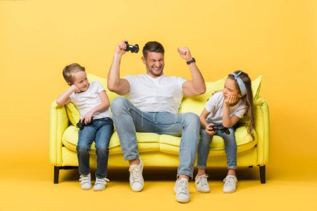Photo for KYIV, UKRAINE - MARCH 4, 2020: excited father and kids playing video game with joysticks on sofa on yellow - Royalty Free Image