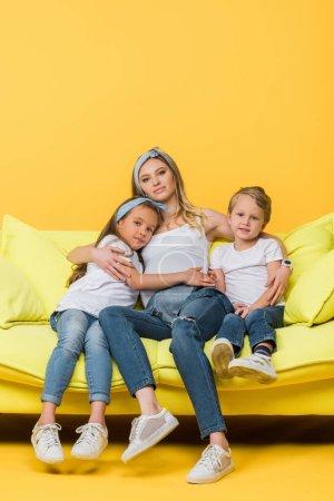 Photo pour Mère enceinte étreignant avec sa fille et son fils sur le canapé jaune - image libre de droit