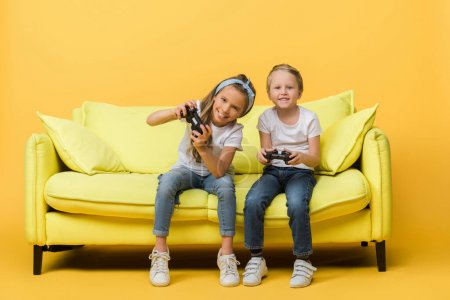 Photo for KYIV, UKRAINE - MARCH 4, 2020: happy siblings playing video game with joysticks on sofa on yellow - Royalty Free Image