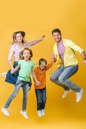 Photo pour Famille excitée sautant et tenant la main sur jaune - image libre de droit