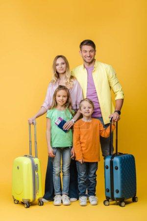 Photo pour Famille souriante de voyageurs avec bagages, passeports et billets sur jaune - image libre de droit
