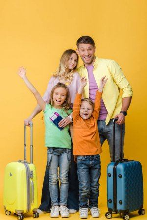 Photo for Cheerful family of travelers with luggage, passports and tickets on yellow - Royalty Free Image