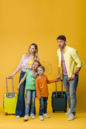 Photo for Happy parents and kids with travel bags, passports and tickets on yellow - Royalty Free Image