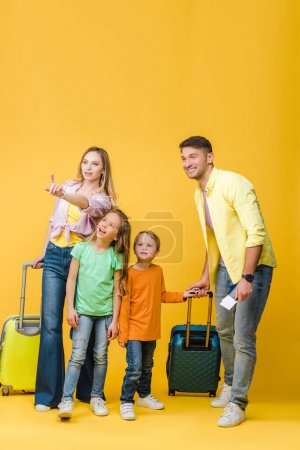 Photo pour Famille heureuse de voyageurs avec bagages, passeports et billets pointant sur jaune - image libre de droit