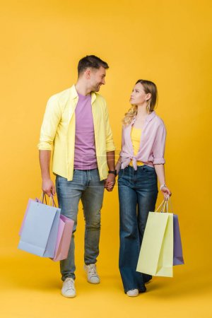 Photo for Beautiful couple holding shopping bags and looking at each other on yellow - Royalty Free Image