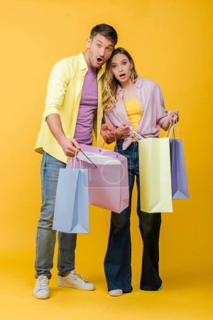 Photo for Beautiful surprised couple holding shopping bags on yellow - Royalty Free Image