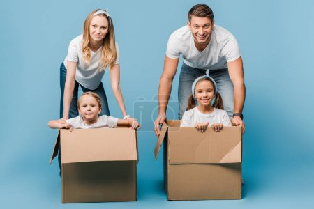 Photo for Smiling parents with children in cardboard boxes for relocation on blue - Royalty Free Image