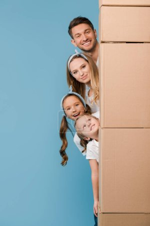 Photo for Happy parents and kids with cardboard boxes for relocation on blue - Royalty Free Image