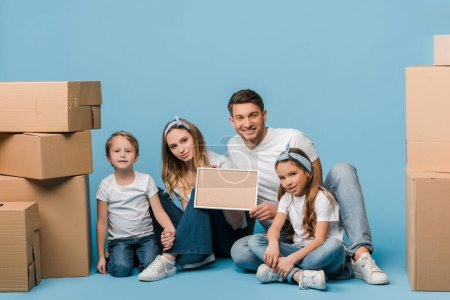 Photo for Happy parents and kids holding frame and sitting on blue with cardboard boxes for relocation - Royalty Free Image