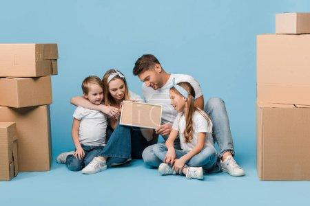 Foto de Padres y niños positivos que tienen marco y están sentados en azul con cajas de cartón para su reubicación. - Imagen libre de derechos