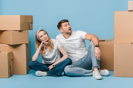 Photo for Dreamy couple sitting with cardboard boxes for relocation on blue - Royalty Free Image
