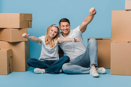 Photo for Excited couple showing thumbs up while sitting with cardboard boxes for relocation on blue - Royalty Free Image