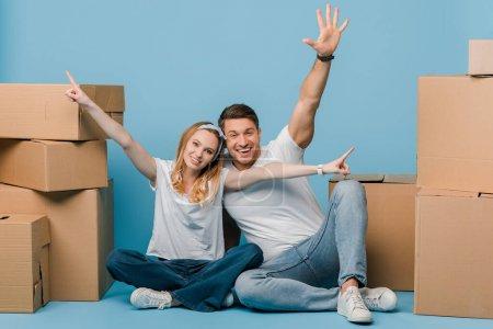 Foto de Pareja feliz apuntando y sentados con cajas de cartón para su reubicación en azul - Imagen libre de derechos