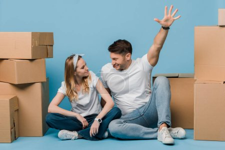 Photo for Excited couple sitting cardboard boxes for relocation on blue - Royalty Free Image