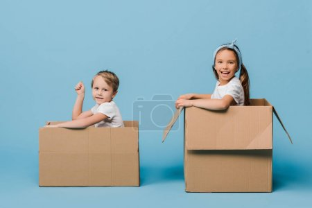 Photo for Adorable cheerful siblings playing in cardboard boxes on blue - Royalty Free Image