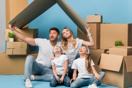 Photo for Happy parents holding carton roof over kids on blue with cardboard boxes for relocation - Royalty Free Image