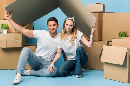 Photo for Beautiful couple holding carton roof over heads while sitting on blue with cardboard boxes for relocation - Royalty Free Image