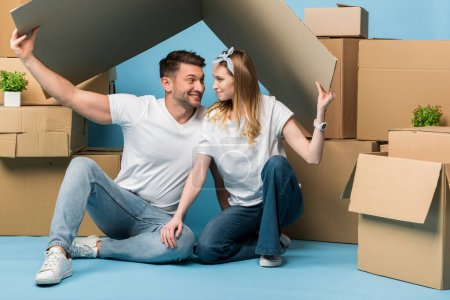 Photo for Happy couple holding carton roof over heads while sitting on blue with cardboard boxes for relocation - Royalty Free Image