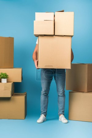 Photo for Man holding cardboard boxes for relocation on blue - Royalty Free Image