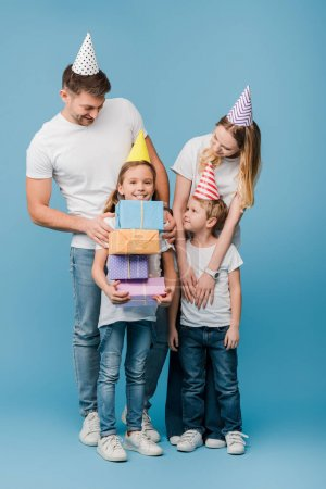 Photo pour Bonne famille dans les casquettes de fête d'anniversaire, fille tenant des boîtes-cadeaux sur bleu - image libre de droit