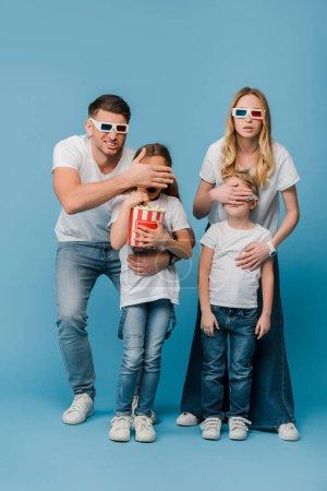 Photo pour Parents choqués dans des lunettes 3D fermant les yeux aux enfants tenant seau de maïs soufflé sur bleu - image libre de droit