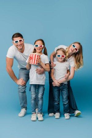 fröhliche Familie schaut Film in 3D-Gläsern und hält Popcorn-Eimer auf blau