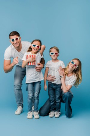 cheerful family watching movie in 3d glasses and holding popcorn bucket on blue