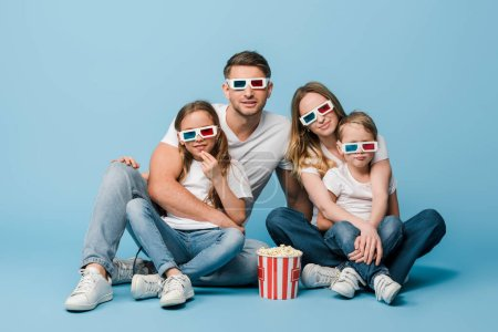 Photo for Happy family watching movie in 3d glasses with popcorn bucket on blue - Royalty Free Image