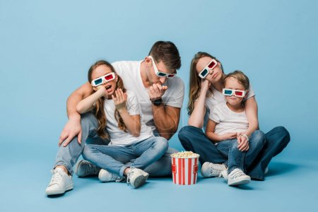 Photo for Confused family in 3d glasses watching movie and holding popcorn bucket on blue - Royalty Free Image