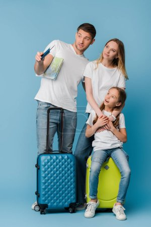 Photo for Parents and shocked daughter with travel bags, map and passports on blue - Royalty Free Image